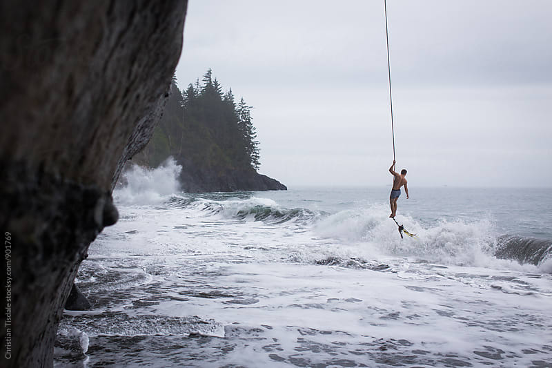 Man hanging on a ropeswing over crashing ocean waves by Christian Tisdale for Stocksy United