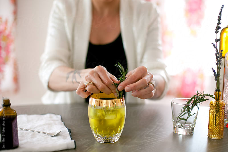 Woman arranging herbs in cocktail by Jennifer Brister for Stocksy United