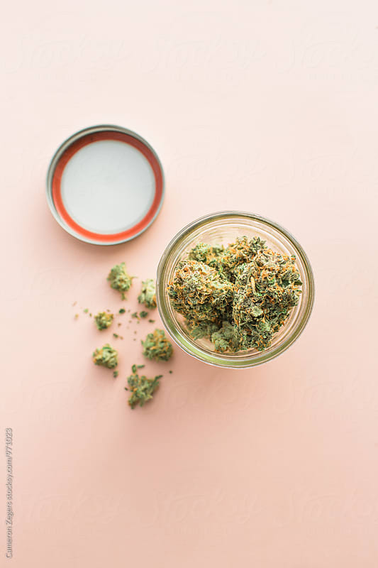 jar of marijuana on pink background by Cameron Zegers for Stocksy United
