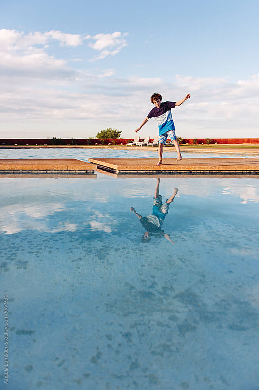 Whistling boy playing with his reflection in a swimming pool by Angela Lumsden for Stocksy United