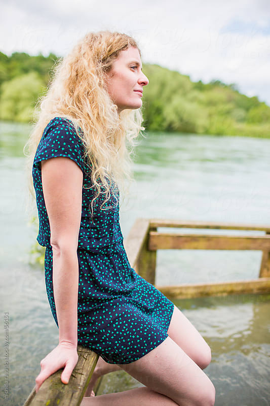 Young woman relaxes sitting along the river by michela ravasio for Stocksy United