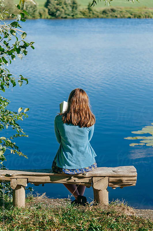 teen girl reading book outside by pond by Deirdre Malfatto for Stocksy United