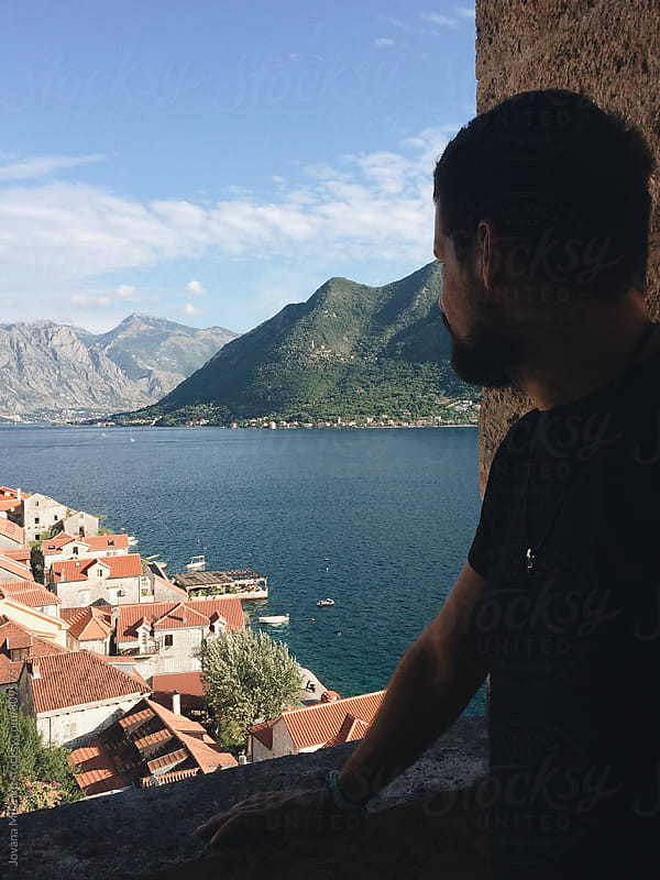 Man observing Perast coastal town of Montenegro by Jovana Milanko for Stocksy United