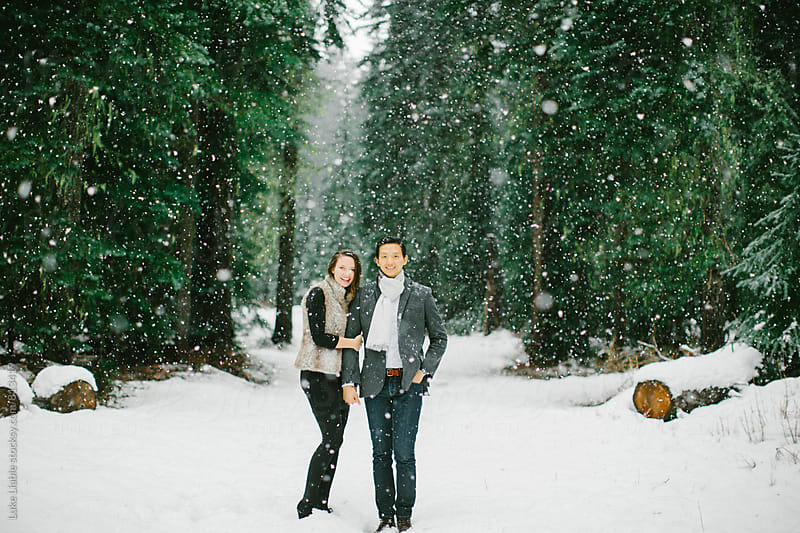Young engaged couple loving the winter snow by Luke Liable for Stocksy United