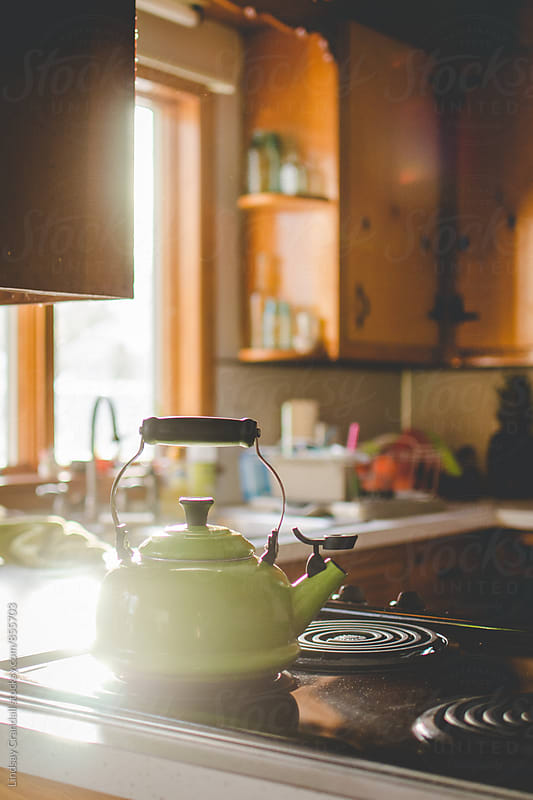 Green tea kettle on the stove in bright sunny kitchen by Lindsay Crandall for Stocksy United