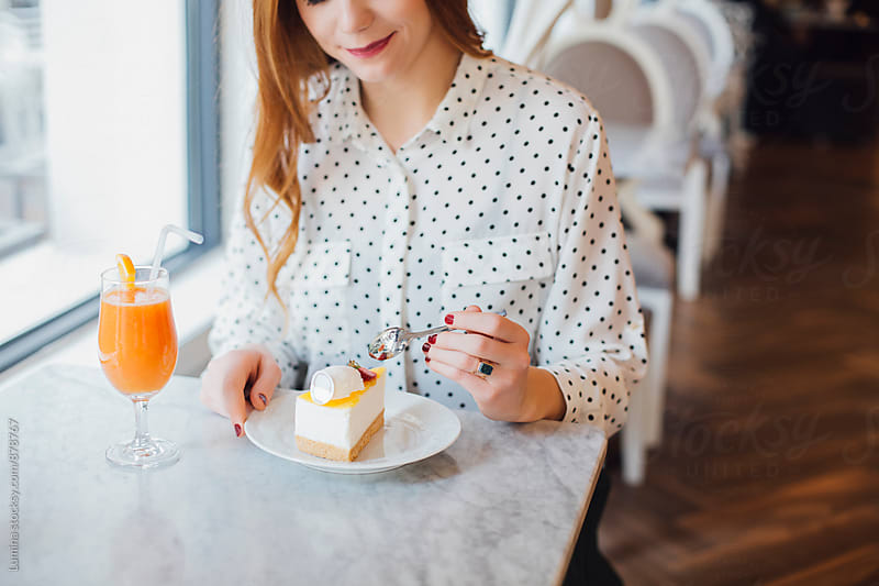 Woman Eating her Dessert and Drinking Orange Juice by Lumina for Stocksy United
