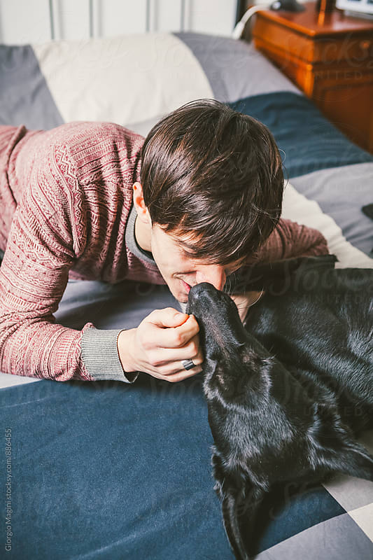 Young Man Cuddling Dog at Home by Giorgio Magini for Stocksy United