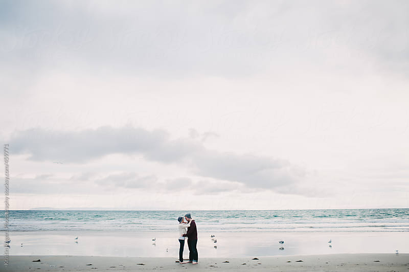 cute couple on date  kissing on cloudy beach day by Kristin Rogers Photography for Stocksy United
