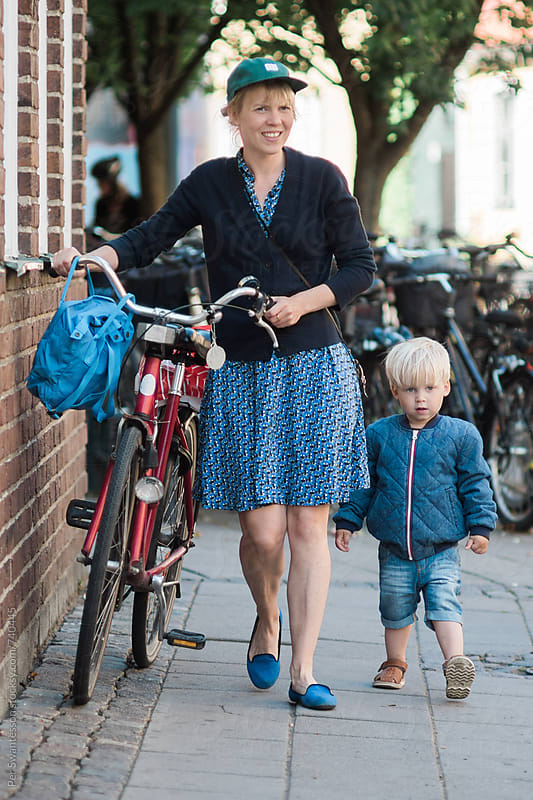Mother and toddler walking together with a bicycle by Per Swantesson for Stocksy United