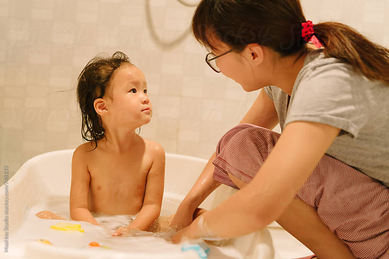 mother giving baby daughter a bath by MaaHoo Studio for Stocksy United