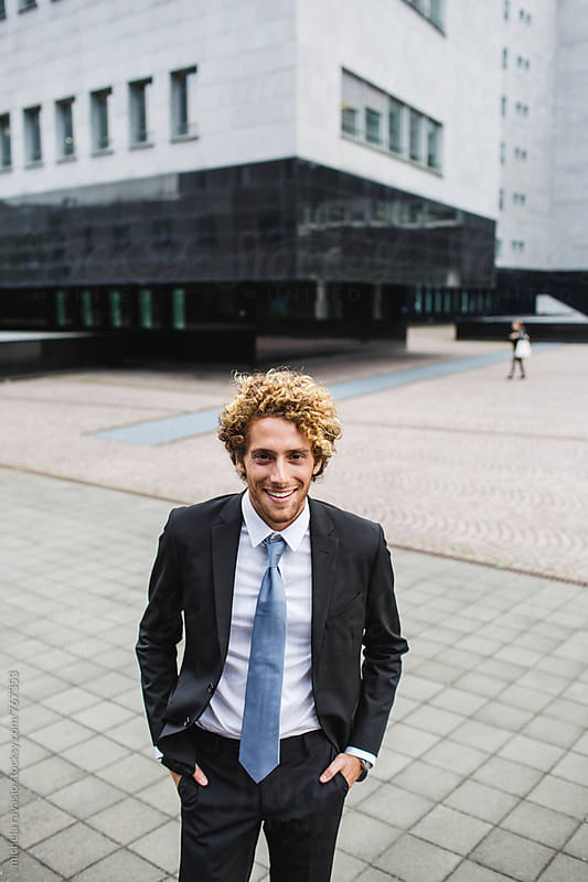Young businessman smiling outside the office by michela ravasio for Stocksy United