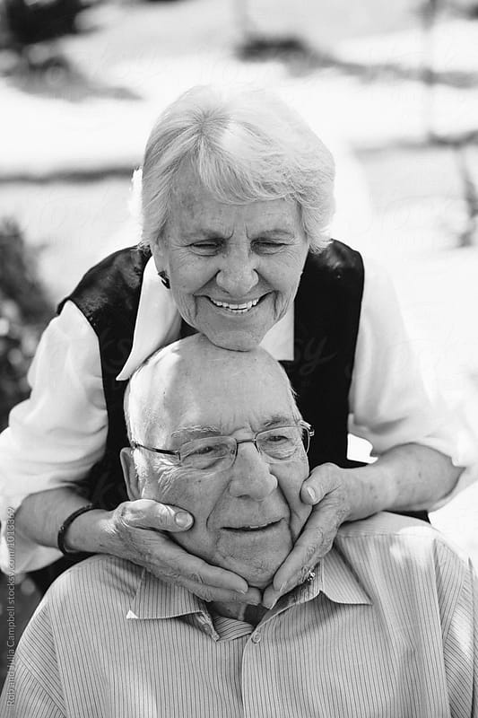 Happy, fun loving elderly couple outside in garden using wheelchair by Rob and Julia Campbell for Stocksy United