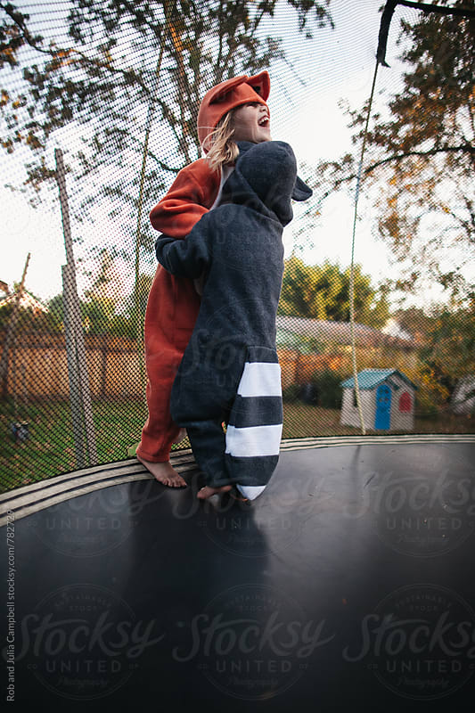 Cute girl in fox and boy in raccoon costume hugging on trampoline by Rob and Julia Campbell for Stocksy United