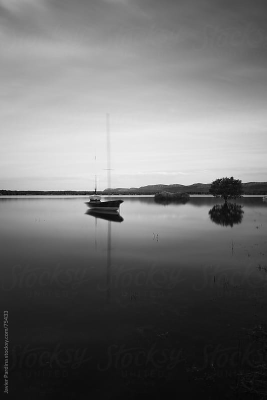 landscape with boats on the lake in black and white by Javier Pardina for Stocksy United