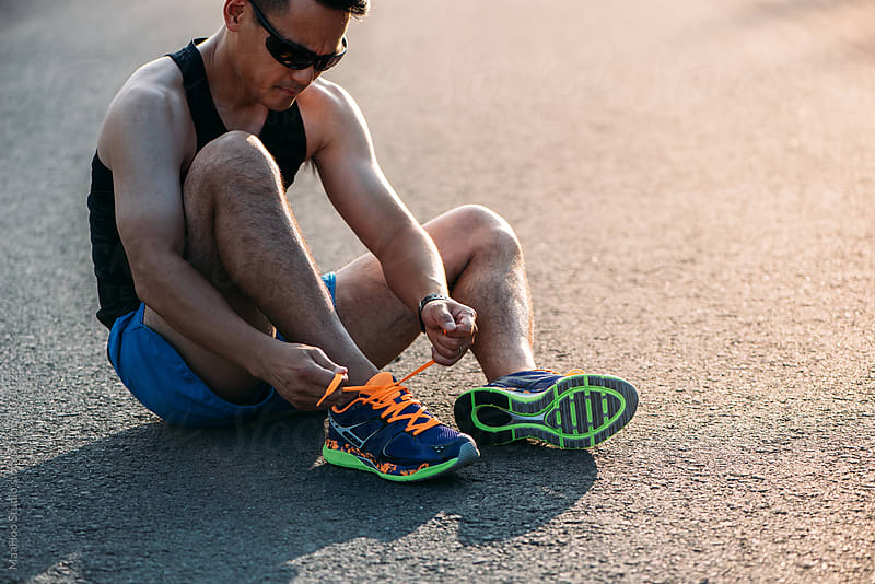 Chinese runner tying his shoelaces by MaaHoo Studio for Stocksy United