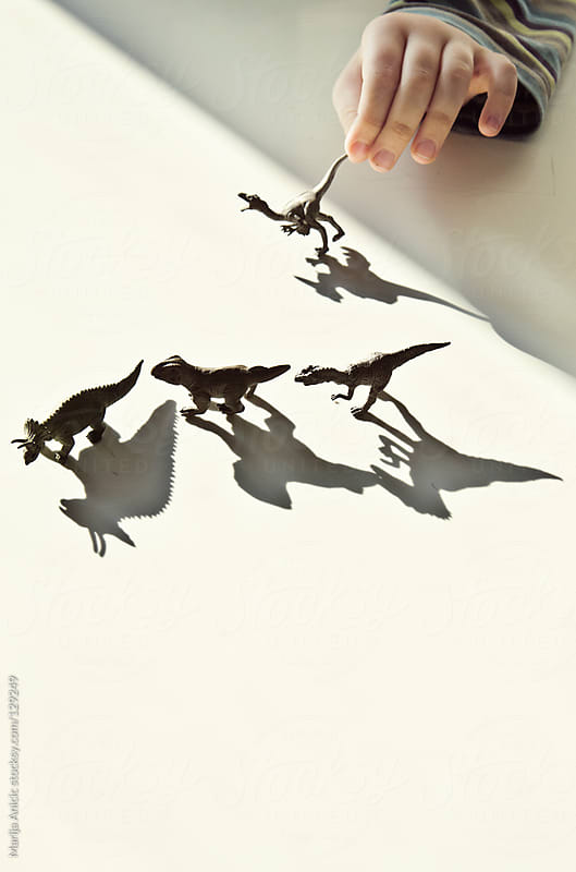 Boy is playing with dinosaurs toys by Marija Anicic for Stocksy United