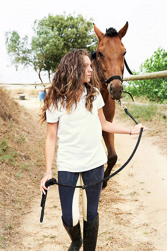 Teen jockey with wavy hair leading horse on strap by Guille Faingold for Stocksy United