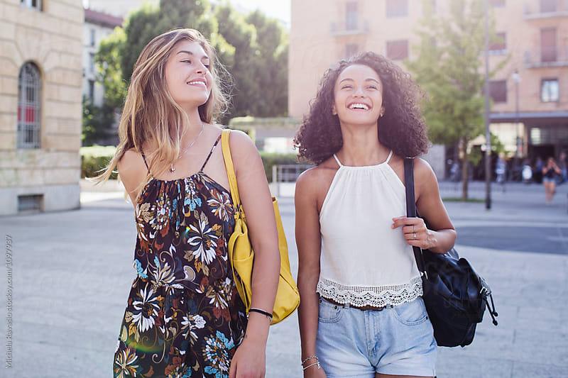 Happy female friends walking around the city by michela ravasio for Stocksy United