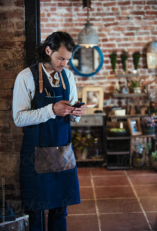 Small artisan business owner texting  by Trinette Reed for Stocksy United