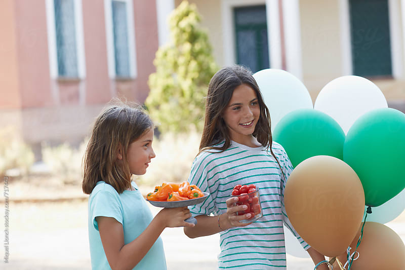 Two girl friends with food and balloons for a party by Miquel Llonch for Stocksy United