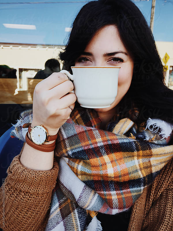 Young Woman Hiding Her Smile Behind A White Coffee Cup by Luke Mattson for Stocksy United