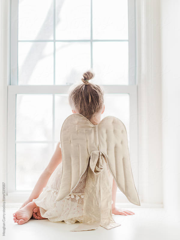little girl playing dress up with angel wings sitting at a window by Meaghan Curry for Stocksy United