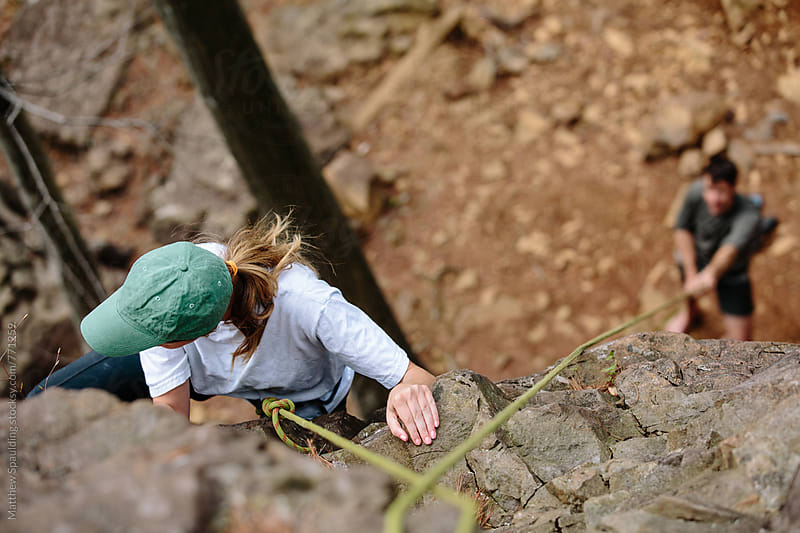 Woman climbing rock outdoors with safety rope by Matthew Spaulding for Stocksy United