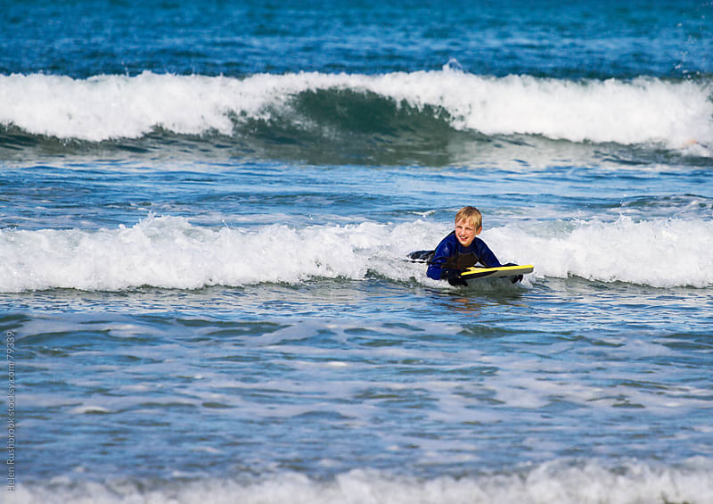 Pre-teen boy body boarding. by Helen Rushbrook for Stocksy United
