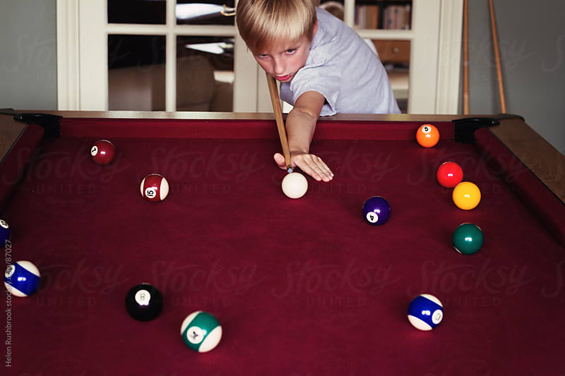 A young boy taking a shot in a game of pool by Helen Rushbrook for Stocksy United