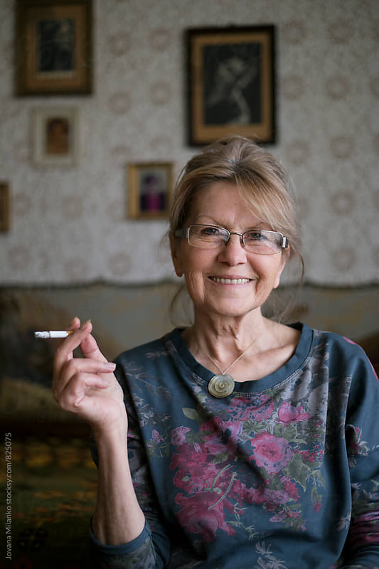Beautiful smily senior woman sitting indoors smoking cigaret by Jovana Milanko for Stocksy United