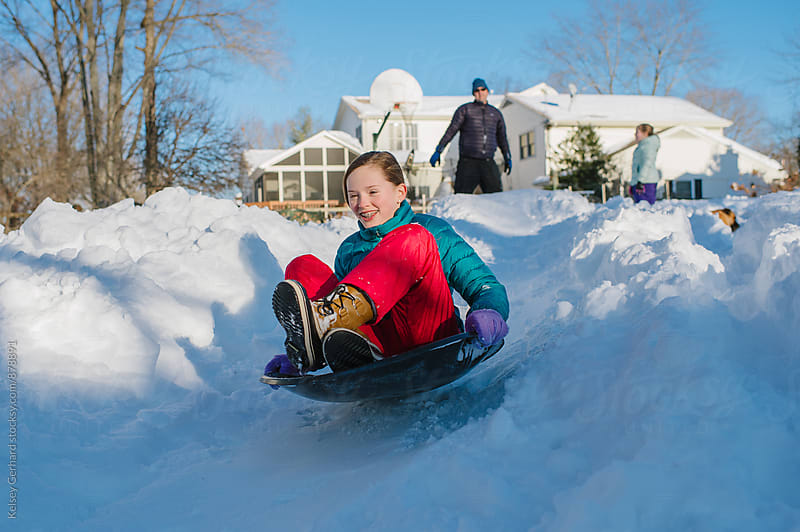 A girl sleds down a snowy residential slope. by Kelsey Gerhard for Stocksy United