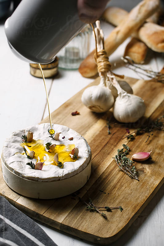 Olive oil being drizzled over Camembert, on a cutting board with ingredients in the background. by Darren Muir for Stocksy United