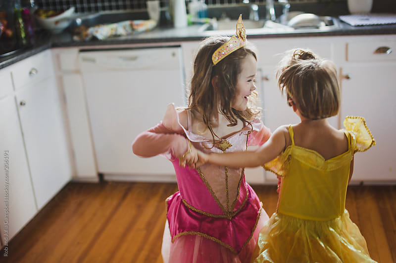 Two preschool-aged sisters dancing in princess dresses by Rob and Julia Campbell for Stocksy United