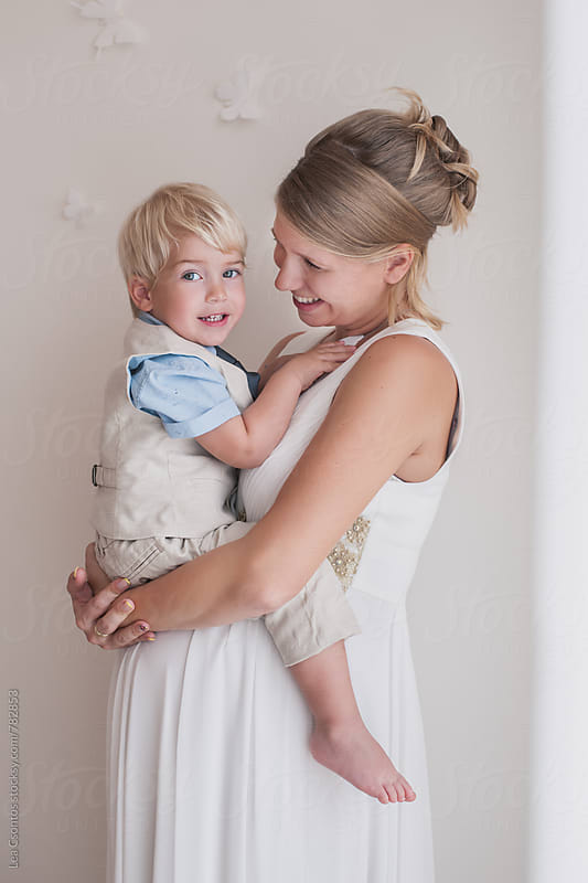 Cute son in her beautiful pregnant mom's arms by Lea Csontos for Stocksy United