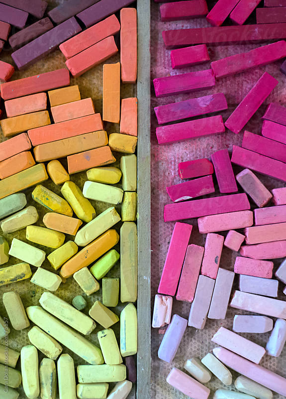 Two trays filled with artist pastels in pinks and yellows by Cara Dolan for Stocksy United