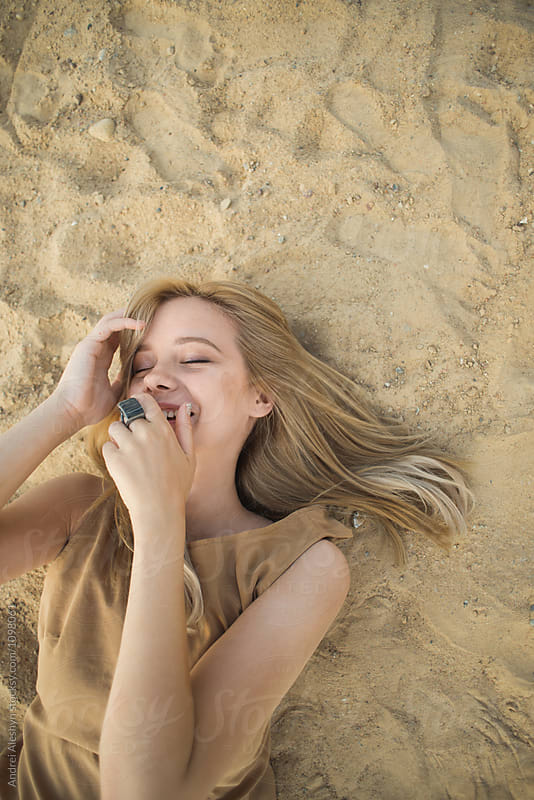 Beautiful young girl laughs while lying on the sand by Andrei Aleshyn for Stocksy United