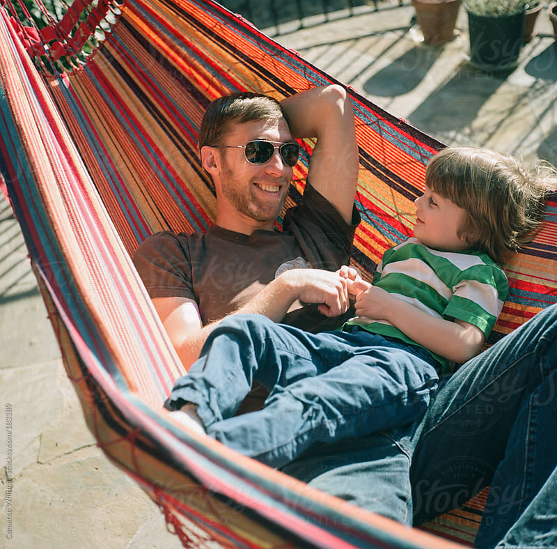 Boy and father in a colorful hammock on the patio by Cameron Whitman for Stocksy United