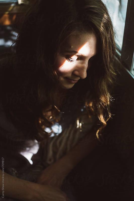 Dark portrait of woman with sunbeam by Carey Shaw for Stocksy United