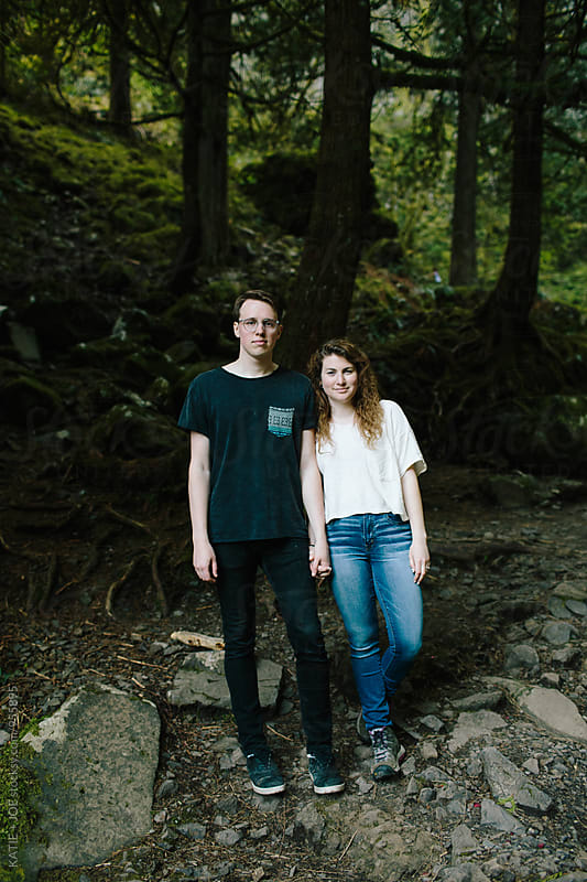 couple standing side by side holding hands in the forest by KATIE + JOE for Stocksy United