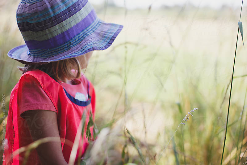 Girl wearing sun hat looking out to grassy field by Rob and Julia Campbell for Stocksy United