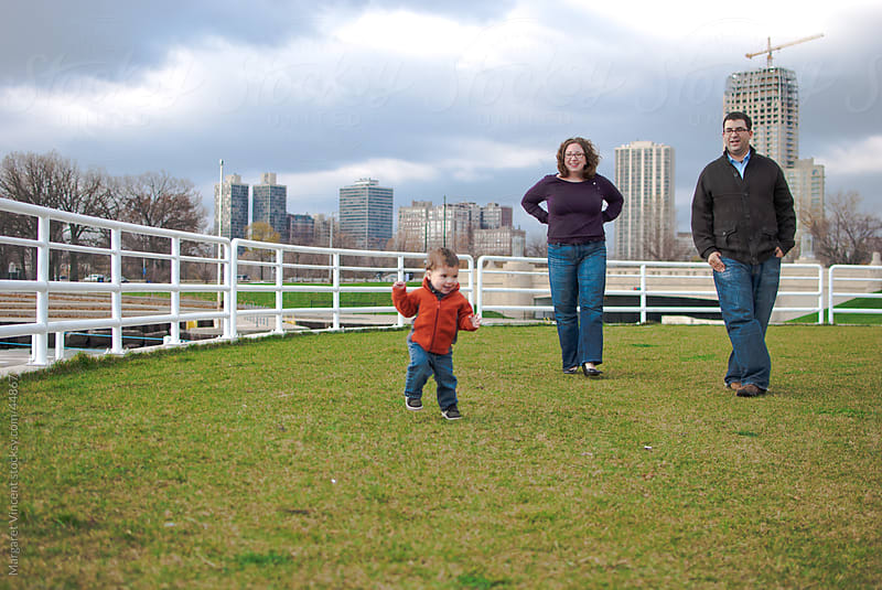 a child walks independently as his parents look on by Margaret Vincent for Stocksy United