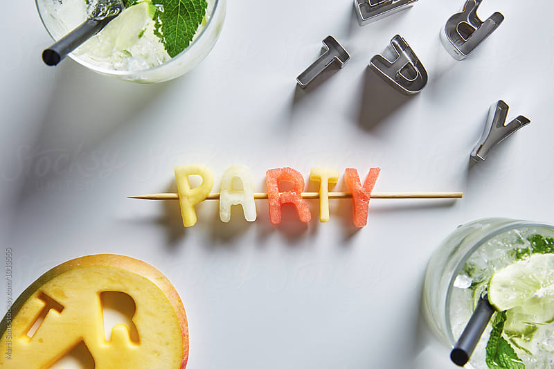 Party word made of watermelon,cantaloup and mango by Martí Sans for Stocksy United
