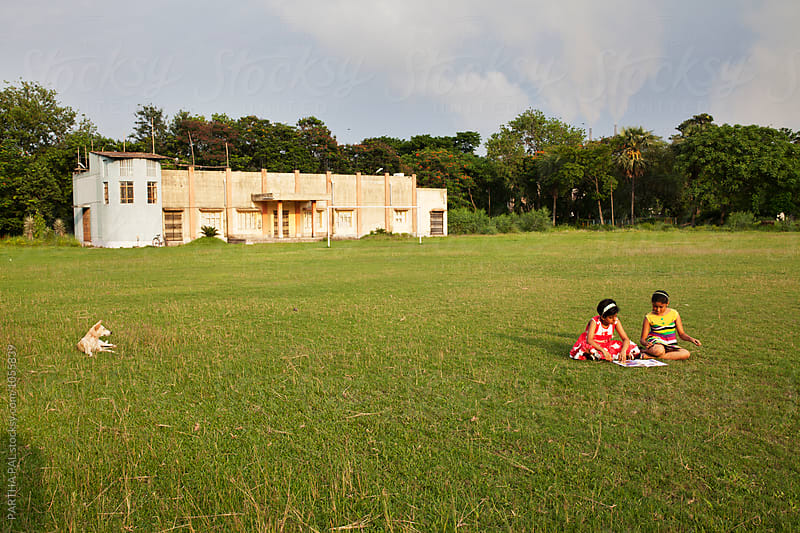 Two teenager studying a book in a green field by PARTHA PAL for Stocksy United