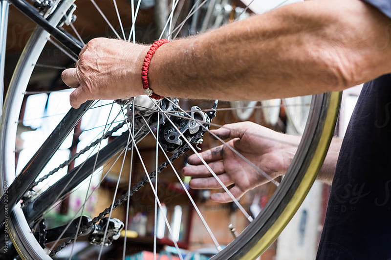 Man Repairing Bicycle Wheel  by Mosuno for Stocksy United