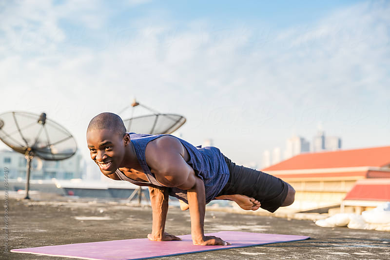 Fit young man smiling during an intense outdoors yoga practice  by Jovo Jovanovic for Stocksy United