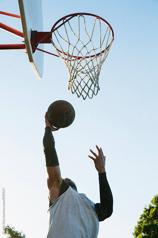 Basketball player in the air for a layup by Curtis Kim for Stocksy United
