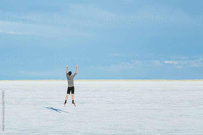 Teenage boy jumping in the air on the vast salt flats of Utah by Adam Nixon for Stocksy United