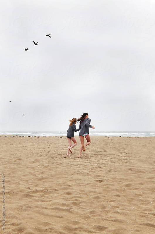 Two Girls Running On An Overcast Beach by Dina Giangregorio for Stocksy United