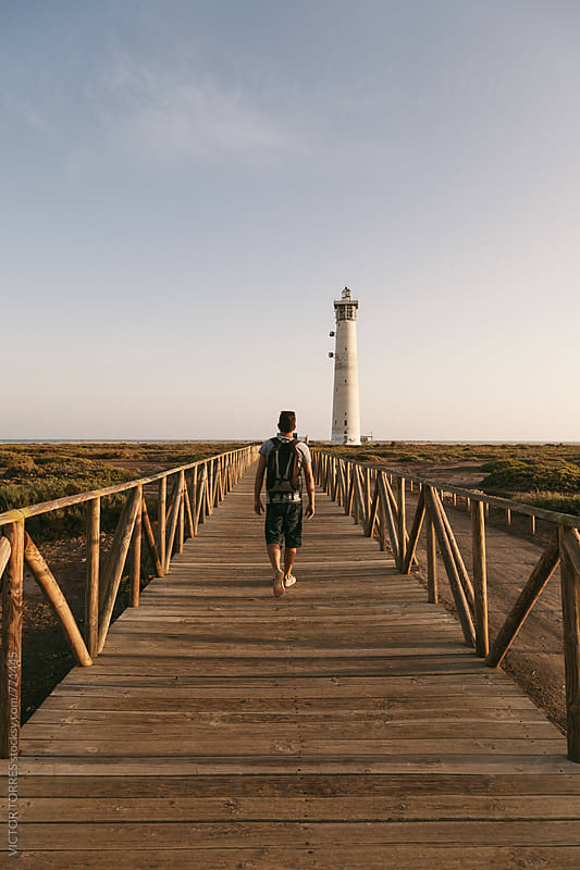 Young Man with Backpack on a Wooden Path to Lighthouse by Victor Torres for Stocksy United