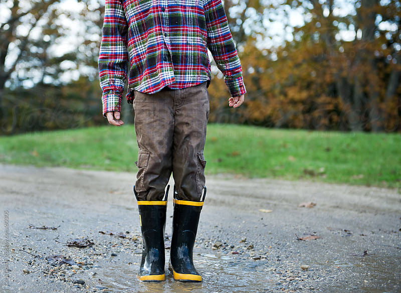 Boy wearing rubber boots stands in a mud puddle by Cara Dolan for Stocksy United